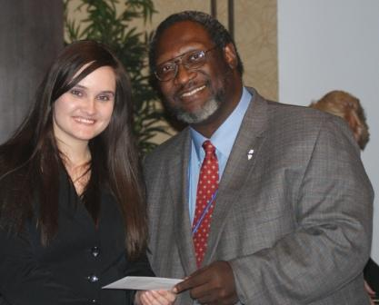 Kiersten Kasey accepts ICCTA's $500 Gigi Campbell Student Trustee Excellence Award scholarship from ICCTA vice president Reggie Coleman.