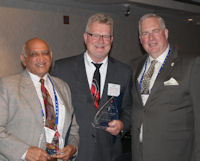 Jody Wadhwa (left) and Richard Anderson (center) receive their 2014 ICCTA Ray Hartstein Trustee Achievement Awards from ICCTA vice president William Kelley.